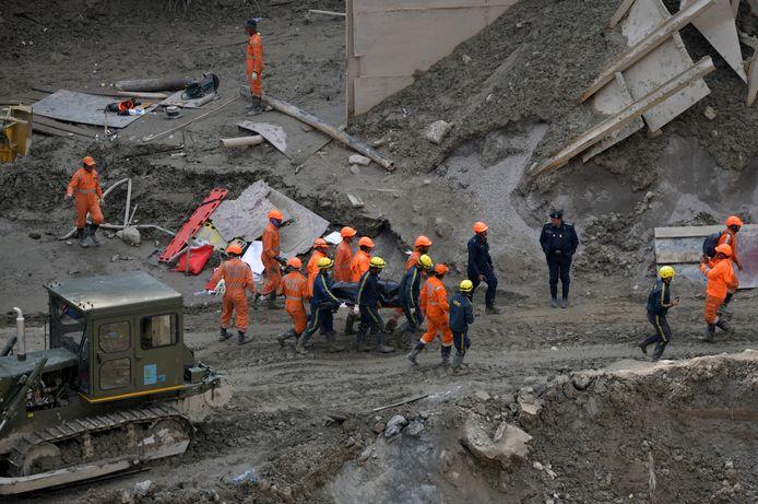 Reddingswerkers met het lichaam van een omgekomen slachtoffer.