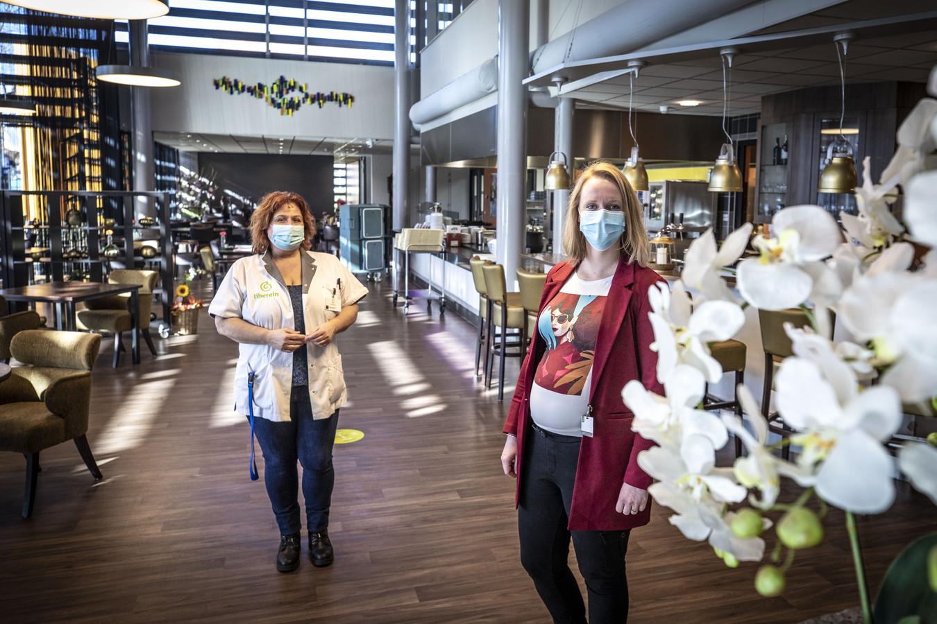 """Teamleider Stephanie Huttenhuis (r) en een verpleegkundig Christel Wiehink in het restaurant dat straks weer open mag. """"Het blijft oppassen, we kunnen geen  feestje stimuleren vanwege gunstige berichten""""."""