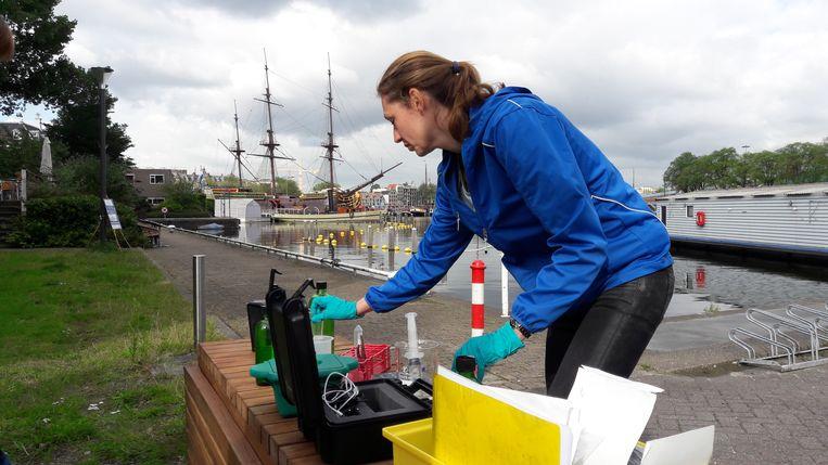 Moleculair analist Fredericke Hannes van Deltares test de waterkwaliteit met het nieuwe apparaat, dat snel controleert op de aanwezigheid van dna van ziekmakende bacteriën. Beeld Deltares