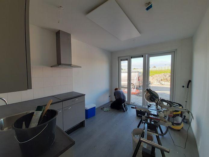 De keuken annex woonkamer, gefotografeerd met een groothoeklens. De huisjes worden compleet met afgewerkte vloeren en wanden en raambekleding opgeleverd.