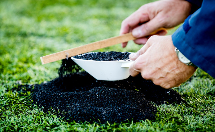 Verzamelde rubberkorrels op een voetbalveld van kunstgras.