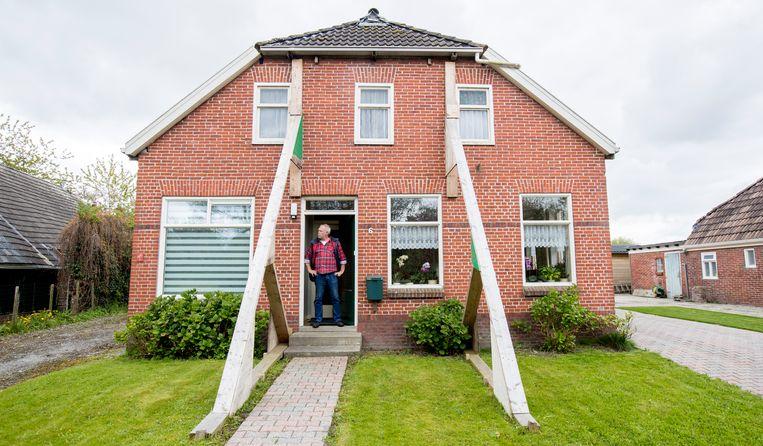 Een bewoner voor zijn beschadigde woning in aardbevingsgebied Loppersum. Beeld ANP