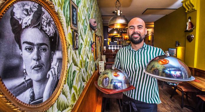 Eigenaar Daniel Muñoz naast een portret van de Mexicaanse kunstenares Frida Kahlo.