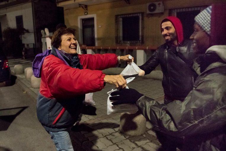 Inwoners delen eten uit aan vluchtelingen. Beeld Photo News