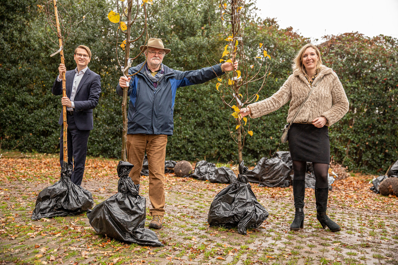 Theo von Piekartz van De Groene Loper Losser-Oldenzaal (midden) en de wethouders Jaimi van Essen (Losser) en Evelien Zinkweg (Oldenzaal) reiken symbolisch de bomen uit aan de zestien buurtinitiatieven die zich hebben aangemeld voor de campagne 'Iedereen een boom'.