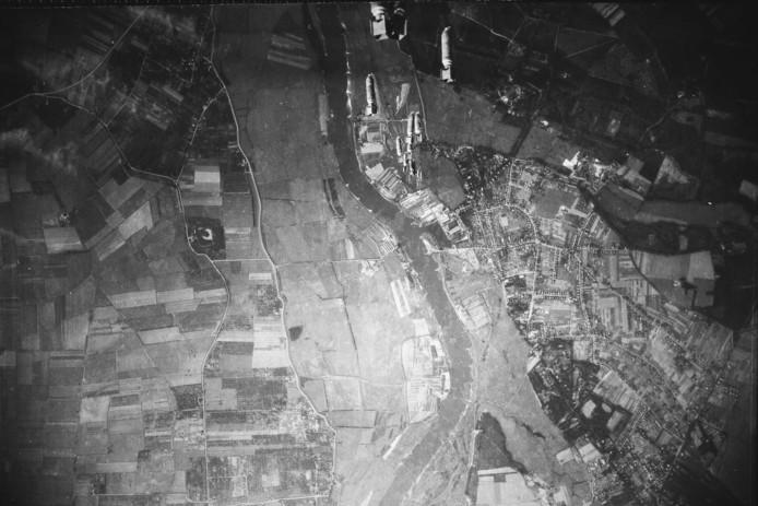 De Amerikaanse bommenwerper vliegt boven Renkum en heeft net de bommen gelost die op weg gaan naar Wageningen. Rechtsboven is Oranje Nassau's Oord te zien, links de Rijn.