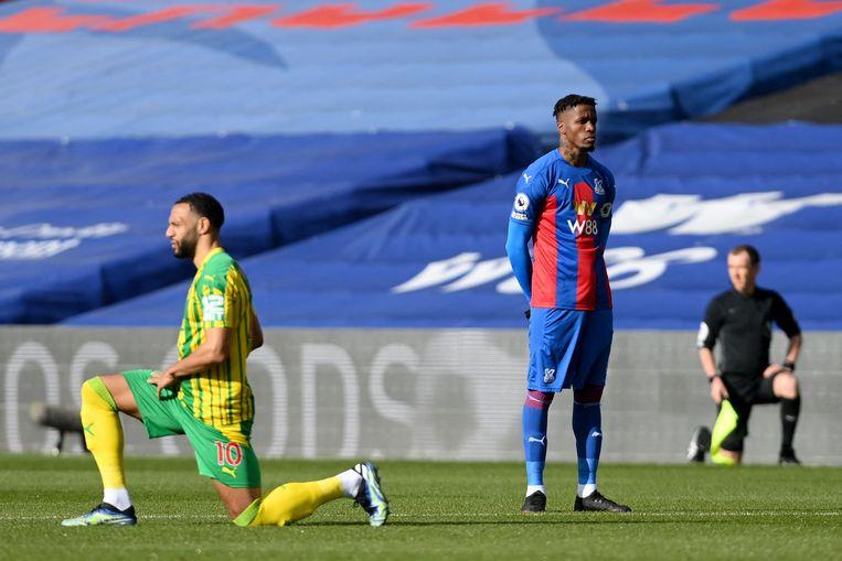 Wilfried Zaha blijft staan terwijl andere spelers en scheidsrechters knielen voor aanvang van de wedstrijd.  Beeld AFP