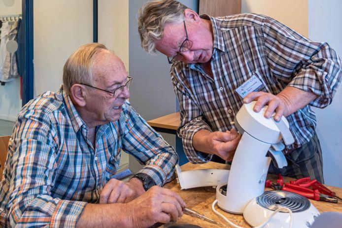 Vrijwilligers repareren een koffiezetmachine.