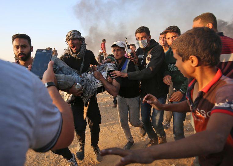 Palestijnen dragen een gewonde protestant weg van de vuurlinie. Beeld AFP