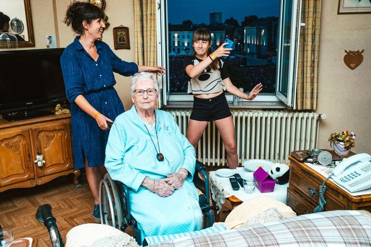 Celine en haar elfjarige dochter Lily kijken samen met Yvonna (94) naar Björk. Beeld Illias Teirlinck