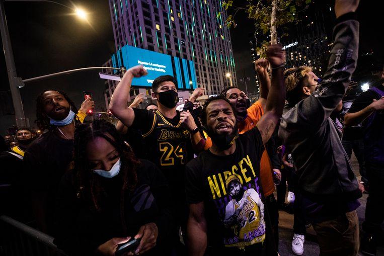 Fans van de Lakers moedigen hun team aan op het terras van een café in Los Angeles.  Beeld EPA