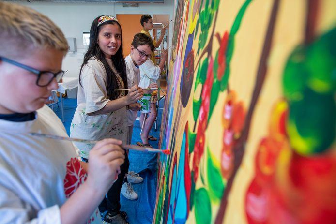 Lazo werkt met de kinderen op Zonnesteen aan de muurschildering.