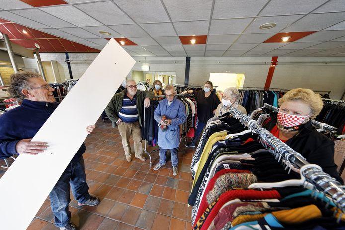 Vrijwilligers aan het werk om de nieuwe kledingbank Gestels Goei Goed op orde te krijgen in de kantine van SCI op Heidelust.