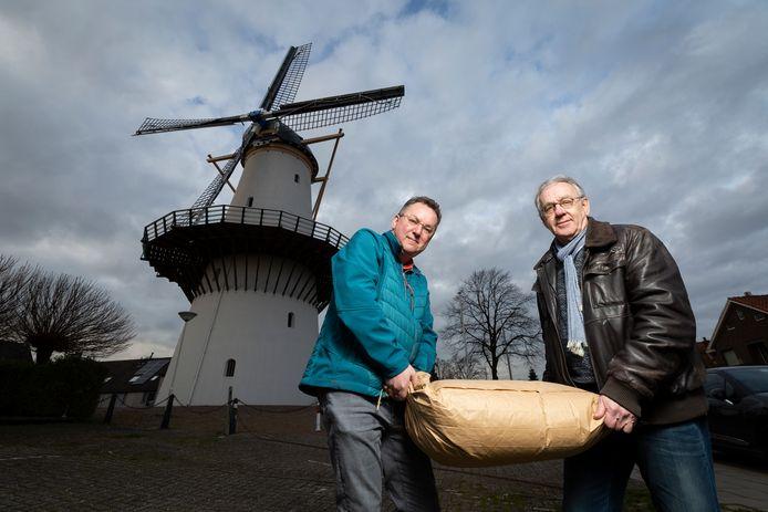 Cor Groen (blauwe jas) en Jacques Boonekamp van Stichting Molen De Hoop lopen met een zak meel van 25 kilo. Foto ter illustratie.