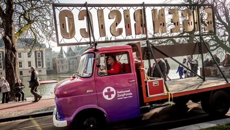 Een auto met de tekst 'Eigen Risico' passeert het torentje in Den Haag in februari 2017, tijdens een manifestatie voor de oprichting van een Nationaal Zorg Fonds. Beeld Freek van den Bergh