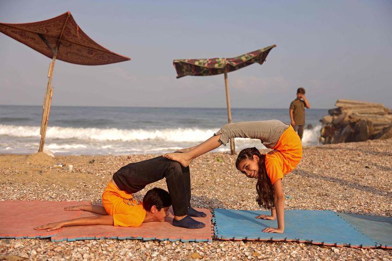 Slangenmensen zijn het, deze jonge Palestijnen die zich in onmogelijke bochten buigen tijdens een training op het strand bij Gaza Stad.  Beeld AFP