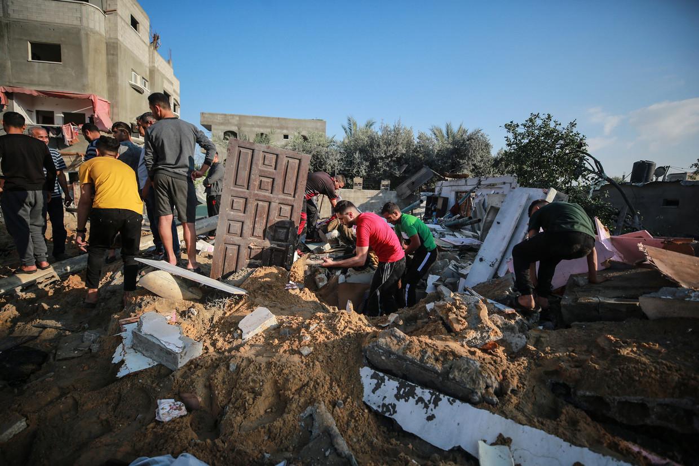Palestijnen in Gaza, op zoek naar bruikbaar materiaal tussen het puin van gebouwen die verdield werden door Israëlische luchtaanvallen, 13 mei 2021. Beeld Anadolu Agency via Getty Images