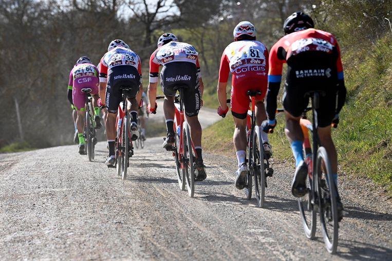 De renners vlammen over een grindweg tijdens de klassieker Strade Bianche in Italië. Beeld BELGA