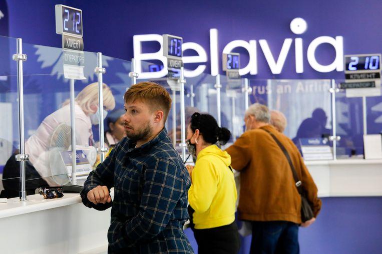 Reizigers in de luchthaven van Minsk, Belarus, leveren hun tickets in nadat het vliegverbod bekend werd gemaakt. Beeld AP