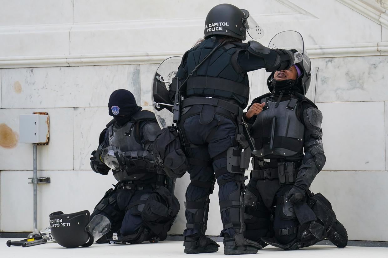 De ogen van een politieagent worden uitgespoeld met water na een confrontatie met de demonstranten.  Beeld AP