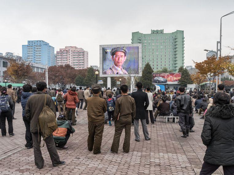 Mensen kijken naar een film op een openbaar scherm in Pyongyang. Op schermen zoals dit worden ook de tests met kernbommen getoond. Beeld rv