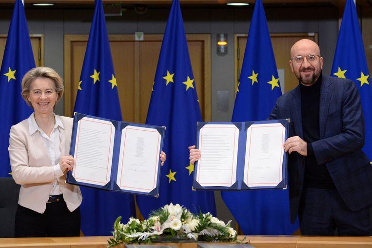 Commissievoorzitter Ursula von der Leyen en EU-president Charles Michel tonen de ondertekende handelsovereenkomst met het Verenigd Koninkrijk in Brussel.  Beeld AP