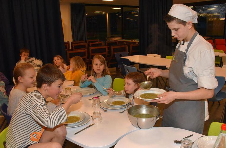 Een leerling dient de soep op voor de kindjes van het internaat.