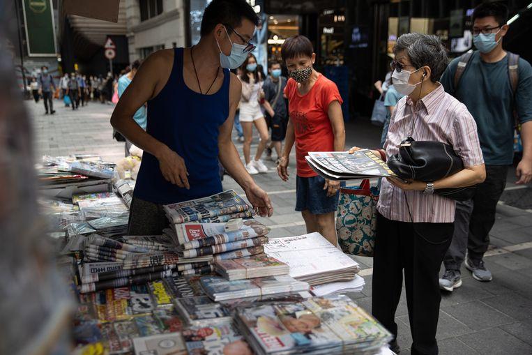Een man koopt vrijdagochtend een exemplaar van de prodemocratische krant Apple Daily bij een kiosk in Hongkong, een dag nadat de politie een inval deed op de redactie en vijf leidinggevenden arresteerde. Beeld EPA