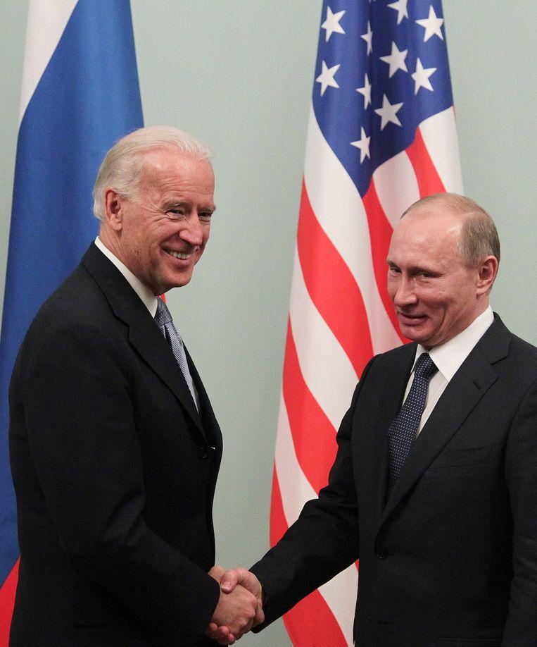 Toenmalig vicepresident Joe Biden en president Vladimir Poetin schudden elkaar de hand tijdens een ontmoeting in Moskou in maart 2011.  Beeld EPA