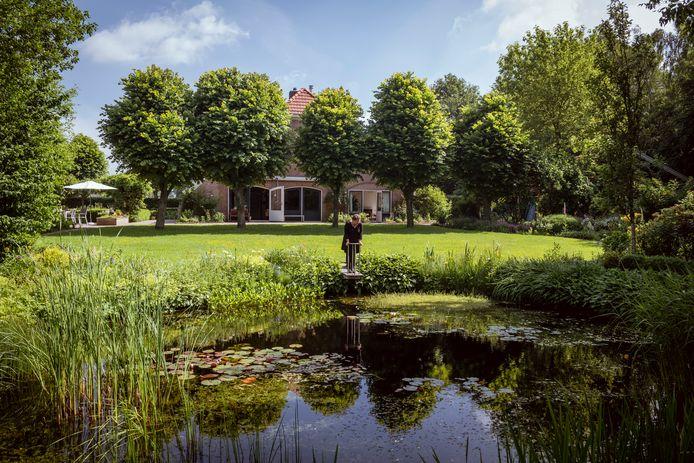 Nelleke Vedelaar bij de vijver in haar royale tuin.