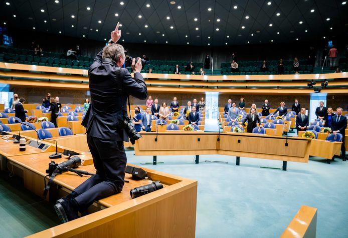 Een fotograaf maakt een groepsfoto tijdens het afscheid van Kamerleden.
