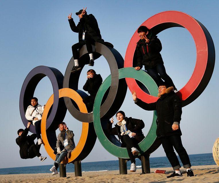 In Gangneung poseren mensen bij de olympische ringen. Beeld anp