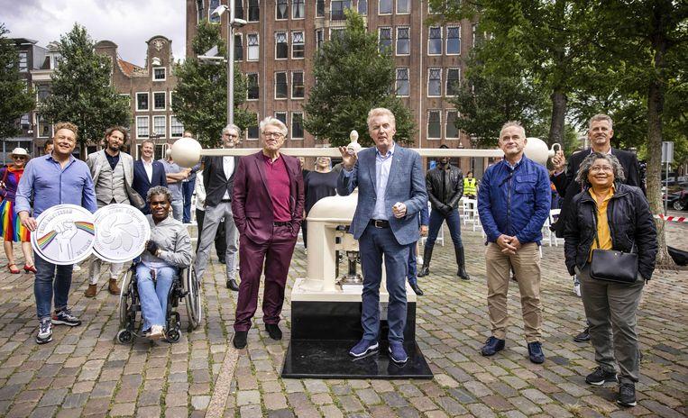 Andre van Duin slaat bij het Homomonument de eerste munt ter ere van 25 jaar Pride Amsterdam, onder toeziend oog van de Pride Ambassadeurs en de LHBTIQ+ gemeenschap. Beeld ANP