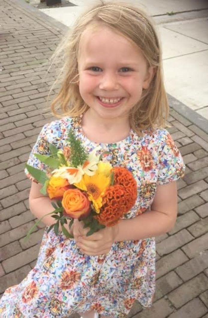Een jongedame staat klaar met haar oranje boeket voor koningin Máxima.