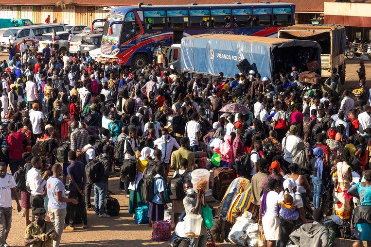 Honderden mensen zoeken op het busstation van Kampala een plek om terug te reizen naar hun geboortegrond.  Beeld Badru Katumba