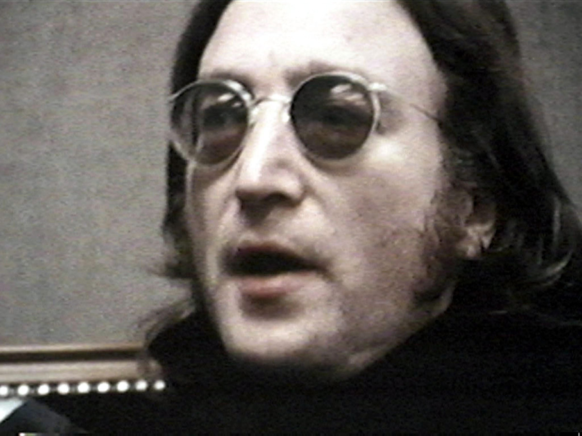 De voormalige Beatle John Lennon met de bekende ronde zonnebril met de groene glazen.