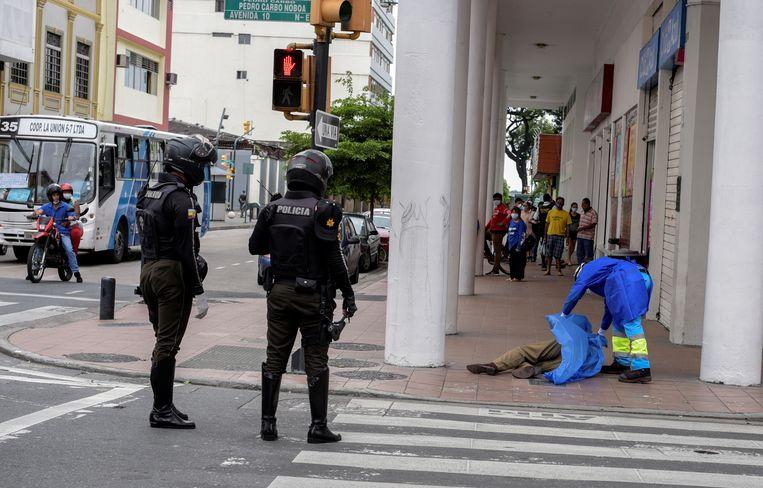 Een ziekenhuismedewerker bedekt het lichaam van iemand die in Guayaquil op straat is overleden, mogelijk aan Covid-19. Beeld Reuters