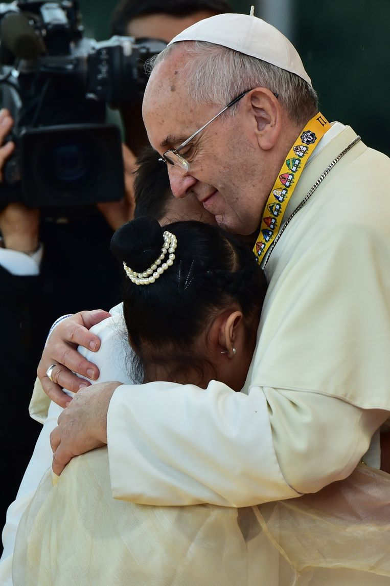 Ook de omhelzing die hij pas nog aan een huilend meisje op de Filippijnen gaf, wijst op een stijlbreuk. Beeld AFP