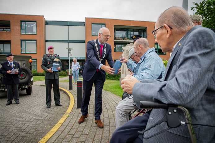 Burgemeester Carol van Eert van de gemeente Rheden deelt vanwege Veteranendag cadeaus uit aan oud-strijders.