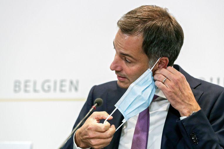 Premier Alexander De Croo (Open Vld) neemt zijn mondmasker af tijdens de persconferentie na het Overlegcomité.  Beeld Photo News