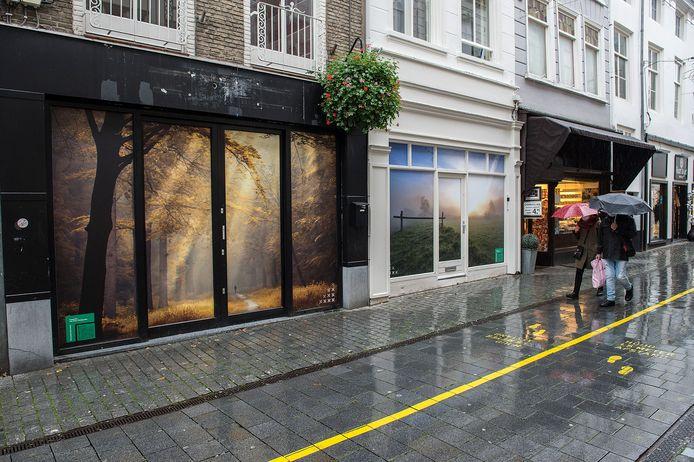 Twee winkels staan leeg en vier te huur in de Korte Brugstraat. De twee leegstaande winkels zijn met grote foto's beplakt.