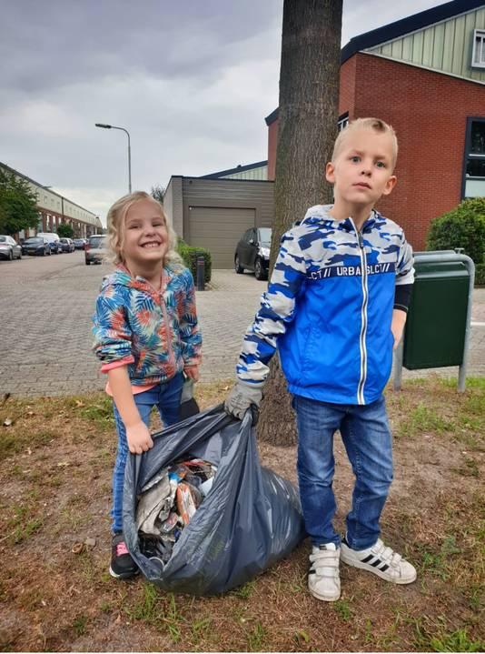 Joshua (7 jaar) en zijn zusje Thirza (5) ruimen op in de Spaarnwoudelaan.