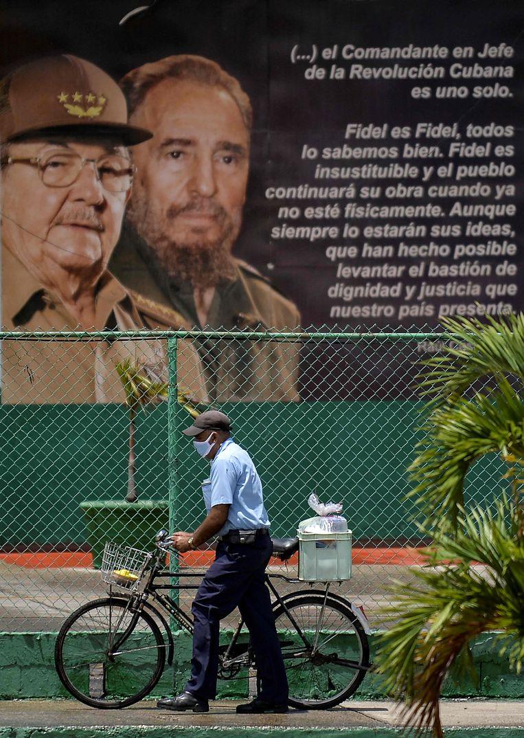Een man loopt met zijn fiets langs een grote poster met de twee Castro's die Cuba zestig jaar domineerden.  Beeld AFP