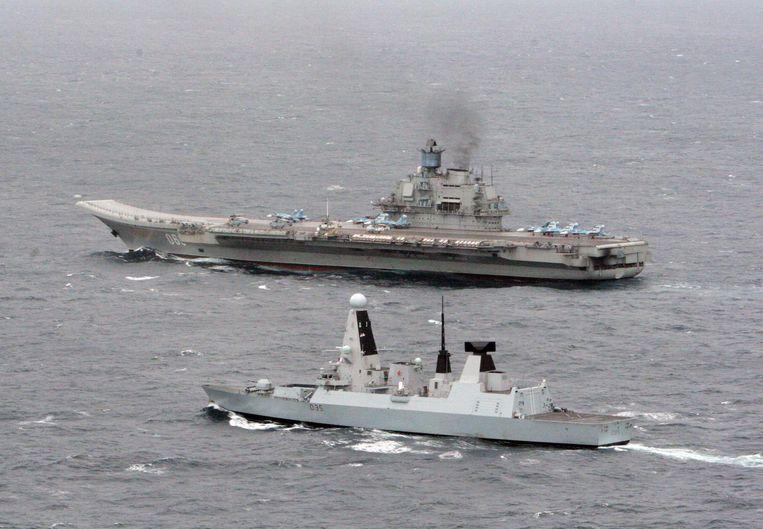 Het Britse oorlogsschip HMS Dragon houdt de Koeznetsov in de gaten in 2014 in het Kanaal. President Poetin wilde de Russische marine versterken met twee Franse helikoptervliegdekschepen, maar Parijs annuleerde de aankoop na de inname van de Krim door de Russen. Beeld EPA
