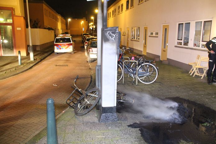 Een parkeerautomaat in Duindorp met op de grond ernaast een smeulende autoband