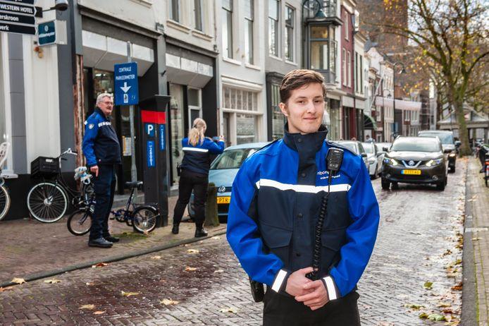 Leerling-toezichthouder Oscar Scheurkogel uit Gouda met op de achtergrond Alicia Huizer uit Boskoop en hun begeleider Arie Anker in de Goudse binnenstad.
