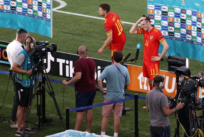 Ondanks de nederlaag tegen Italië staat Gareth Bale na afloop lachend de pers te woord.
