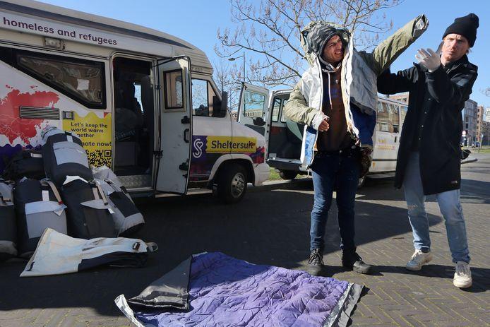 De dakloze Fazlullah (35) krijgt uitleg over een sheltersuit door Bas Timmer (r), oprichter van Sheltersuit Foundation. Twintig van deze pakken die extra bescherming bieden tegen kou en regen zijn uitgedeeld in Breda. Het straatteam van de SMO zorgt voor de verdeling.