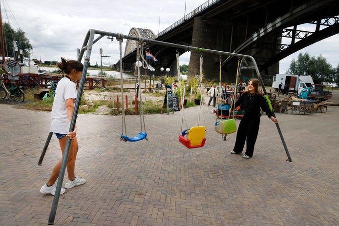 Elze en Charlotte slepen de schommel terug bij de terugverhuizing van de Kaaij. Nijmegen, 2-8-2021 . GV