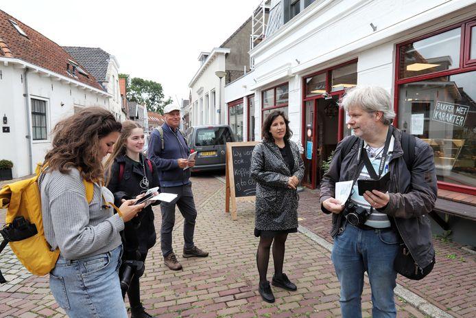 Dichter Ronald van Ham (rechts) luistert in het stadje Geervliet naar zijn eigen bijdrage van de literaire podcastwandeling.